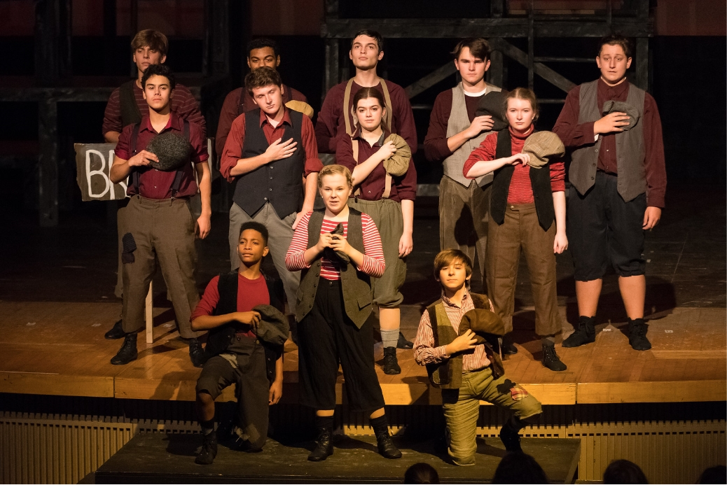 Newsies with hands over their hearts